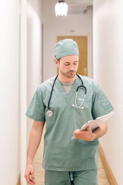 doctor-walking-down-hallway-with-clipboard